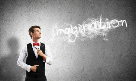 Horizontal shot of confident and young businessman in smart-casual wear smoking pipe while standing against gray dark wall and imagination word made from smoke on background. Imagens - 114303850
