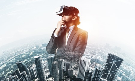 Young handsome businessman in virtual helmet against cityscape background Imagens - 114309320