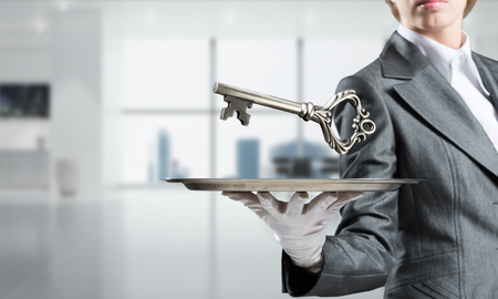 Cropped image of waitresss hand in white glove presenting big key on metal tray with office view on background.