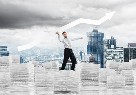 Confident young businessman in suit standing on paper columns with huge white banner in hands which pointing away and with modern cityscape view on background Banco de Imagens - 114303988