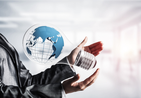 Closeup of business woman in suit holding in hands lightbulb with Earth globe inside. Sunlight on office view background. Stock Photo