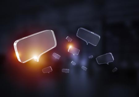 Glänzende Sprechblase aus Glas auf dunklem Hintergrund. Gemischte Medien