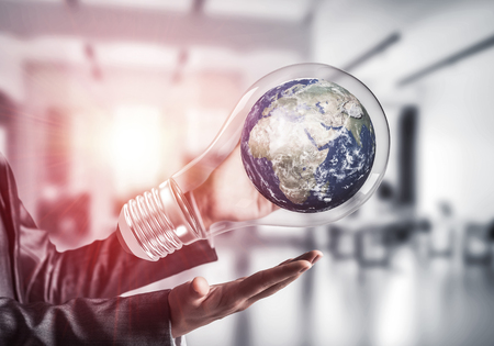Closeup of business woman in suit holding in hands lightbulb with Earth globe inside. Sunlight on office view background