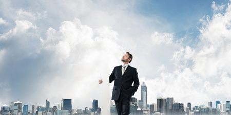 Horizontal shot of young businessman in suit keeping big white arrow in hands while standing against modern cityscape view. Modern business concept Stok Fotoğraf