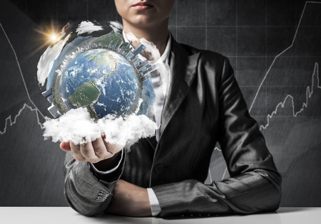 Closeup of businessman in suit keeping in hands Earth globe with buildings, business sketches on background. Elements of this image are furnished by NASA.