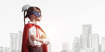 Little confident child in mask and cape plays cool superhero