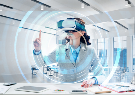 Horizontal shot of beautiful and young business woman in suit using virtual reality headset with digital security interface while standing inside office.