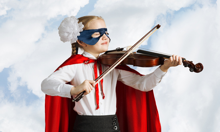 Little confident child in mask and cape plays violin against sky background