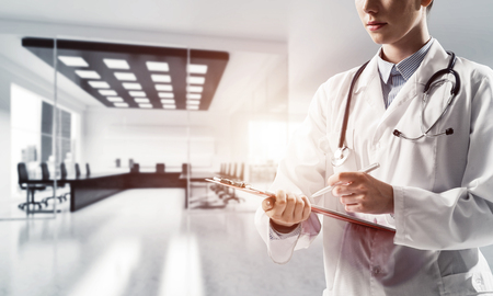 Side view of confident woman doctor in medical uniform writing into the notebook while standing inside bright office building. Medical industry concept
