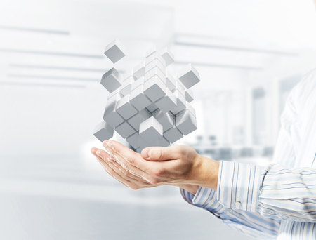 Close of businessman hand holding cube figure as symbol of innovation. 3D rendering Banque d'images