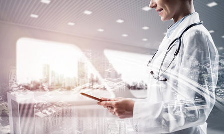 Double exposure of confident female doctor in white coat standing at hospital building with laptop in hands and cityscape view. Modern gadgets for medical industy employee Stock Photo