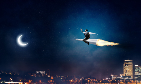 Conceptual image of young businessman in suit flying on rocket with night cityscape and blue sky on background.