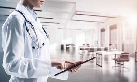 Close up of successful female doctor touching tablet with finger while standing indoors of white hospital building . Medical industry concept by means of confident doctor