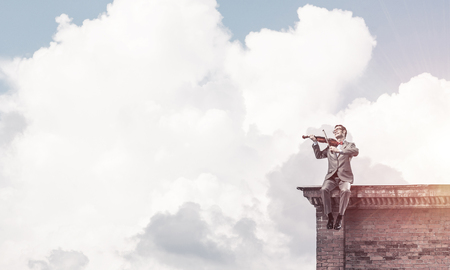 Young man wearing suit and glasses sitting on roof and playing violin Stock Photo