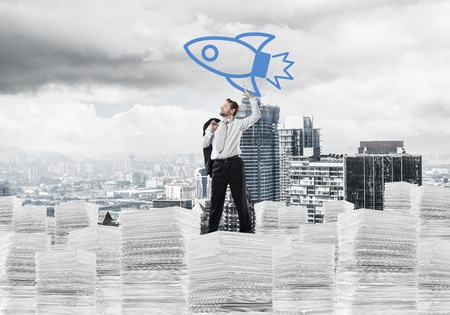 Horizontal shot of successful and young businessman in suit throwing in the air big drawn rocket while standing on paper column with modern cityscape view on background.