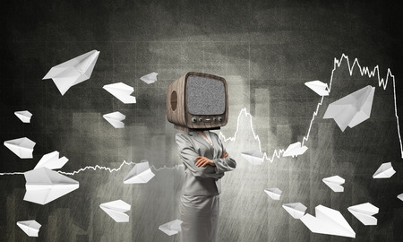 Business woman in suit with old TV instead of head keeping arms crossed while standing against flying paper planes and analytical charts drawn on dark wall on background. Stock Photo