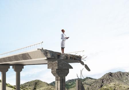 Conceptueel beeld van vrouwelijke arts in wit steriel pak staande op de rand van de gebroken brug met landschapsmening op de achtergrond. Medisch industrieconcept Stockfoto