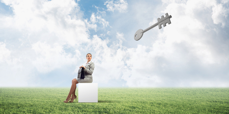 Elegant businesswoman with suitcase in hand sitting on white cube and stone key symbol