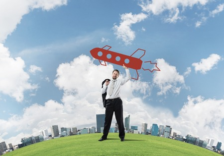 Horizontal shot of successful and young businessman standing on green meadow and throwing huge rocket in the air with cloudy skyscape view on background. Reklamní fotografie