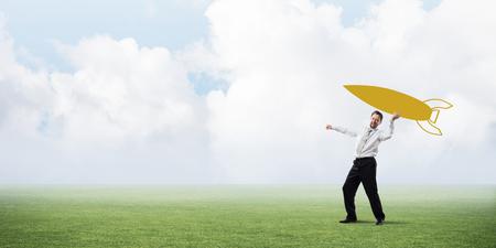Horizontal shot of successful and young businessman standing on green lawn and throwing huge rocket in the air with cloudy skyscape view on background