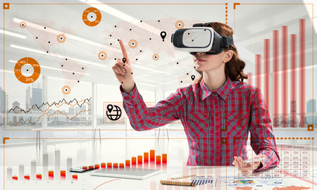 Young woman in checkered shirt using VR headset with digital media interface while sitting inside bright office building. Virtual reality technologies for education Stock Photo - 114914456