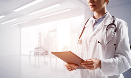 Medical industry conceptual image. Close up of young woman doctor holding modern tablet in hands while standing inside of white hospital building. Banco de Imagens