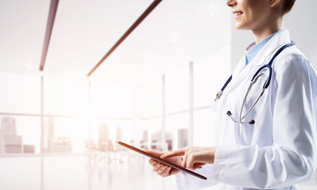 Cropped image of young woman doctor touching tablet screen with finger while standing inside bright medical office building with sunlight on background. Medical industry concept