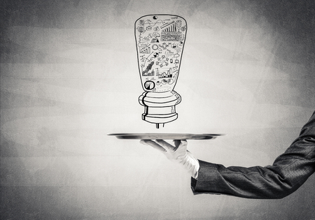 Closeup of waitresss hand in glove presenting sketched business plan in form of lamp on metal tray with gray wall on background.