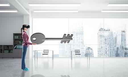 Young woman in virtual reality helmet looking at stone key symbol. Mixed media