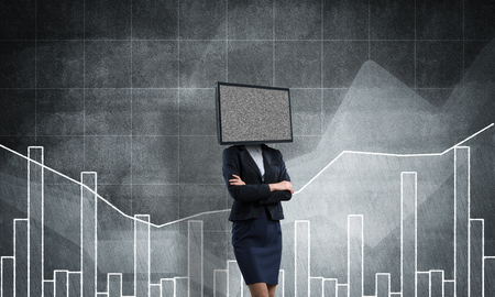 Business woman in suit with TV instead of head keeping arms crossed while standing against analytical charts drawn on dark wall on background.