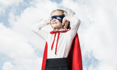 Little child wearing mask and cape closing her ears with hands
