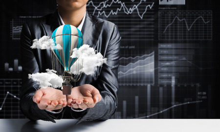 Closeup of business woman in suit presenting flying aerostate among clouds in her palms with business sketches on background. 3D rendering. Imagens