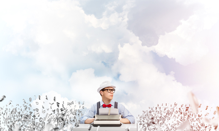 Young man writer in hat and eyeglasses using typing machine while sitting at the table among flying letters with cloudy skyscape on background. Imagens