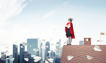 Young girl in superhero costume standing on house brick roof. Mixed media