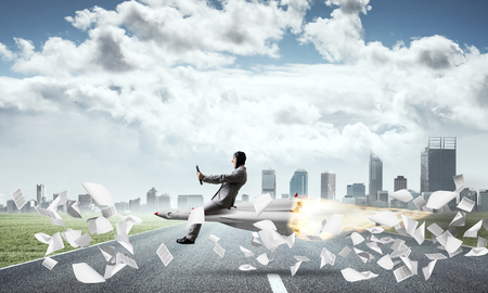 Conceptual image of young businessman in suit flying on rocket above asphalt road and among flying papers with cityscape and blue sky on background.