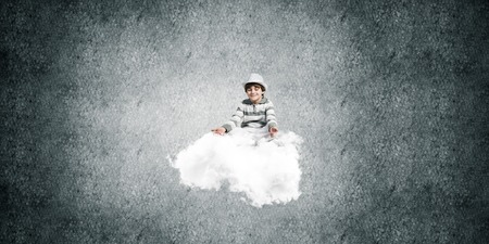 Young little boy keeping eyes closed and looking concentrated while meditating on flying cloud in the air with gray dark wall on background. Stock Photo