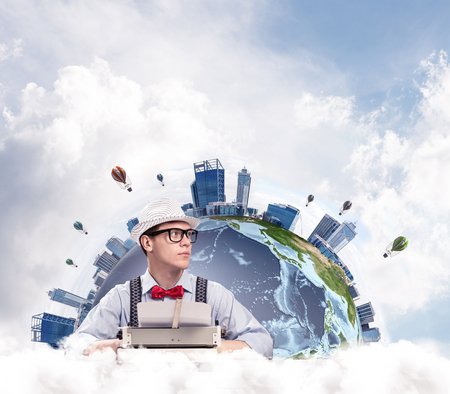 Portrait of man writer looking away and using typing machine while sitting at the table with panoramic Earth and cloudy skyscape on background