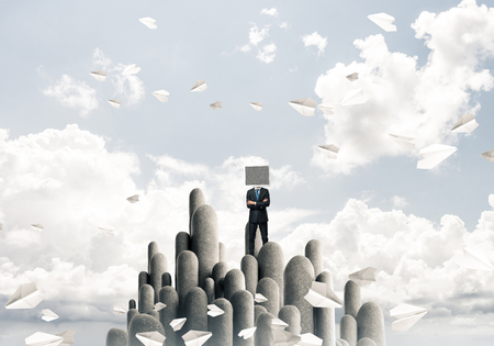 Businessman in suit with monitor instead of head keeping arms crossed while standing on the top of stone columns among flying paper planes with beautiful landscape on background. 3D rendering. Stock Photo