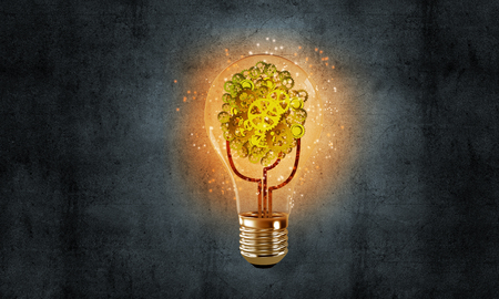Glowing glass lightbulb with multiple gears inside with dark grey wall on background. 3D rendering.