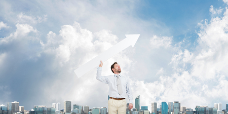 Horizontal shot of young businessman throwing big white arrow in the air while standing against modern cityscape view and cloudy sky on background Stock Photo