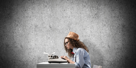 Side view of young beautiful woman writer in hat and eyeglasses using typing machine while sitting at the table against gray concrete wall on background.