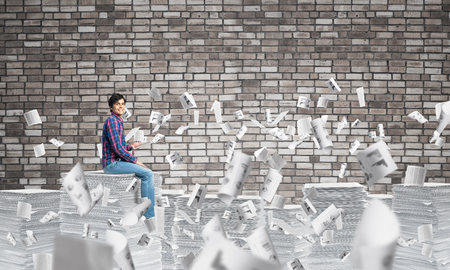 Young man in casual clothing sitting among flying paper documents with grey brick wall on background. Mixed media.