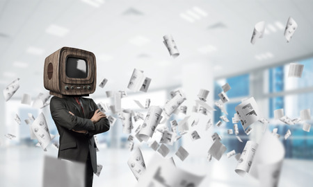 Cropped image of businessman in suit with old TV instead of head keeping arms crossed while standing among flying papers inside office building. Stock Photo