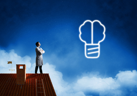 Professional medical industry employee in white medical suit interracting with glowing screw symbol in the air while standing on brick roof and night sky view on background. Stock Photo