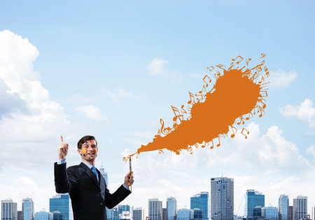 Young and successful businessman in black suit holding paintbrush in hand and smiling while standing with orange liquid musical splash with against modern cityscape view on background.