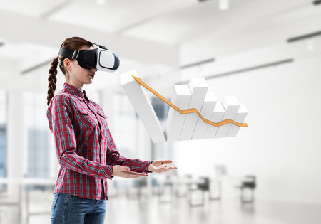 Young woman in virtual reality helmet and graph white symbol. Mixed media Stock Photo