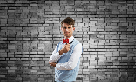 Horizontal shot of confident and young businessman in smart-casual wear smoking pipe while standing against gray brick wall on background.