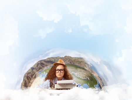 Young woman writer in hat and eyeglasses using typing machine while sitting at the table with Earth globe and cloudy skyscape on background. Elements of this image furnished by NASA