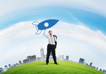 Conceptual image of young confident businessman in suit launching big blue rocket from his hand while standing on green meadow with cloudy skyscape view on background.