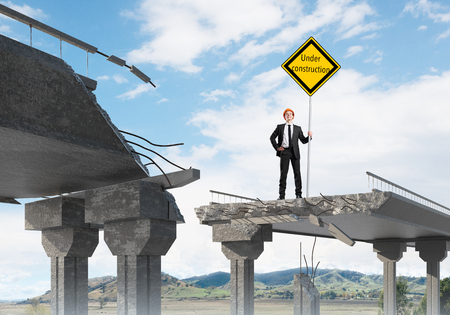Young engineer in helmet holding under construction sign while standing on broken bridge with skyscape and nature view on background. 3D rendering.
